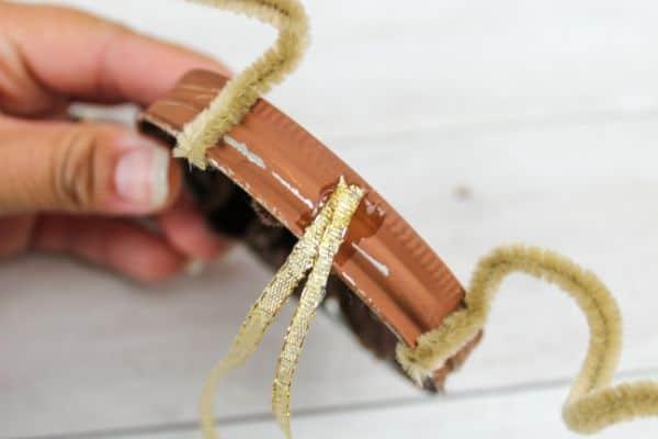 adding a hanger to DIY Mason Jar Lid Reindeer Ornament