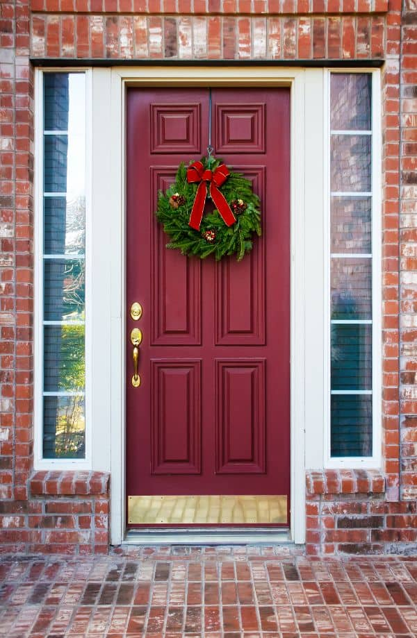 adding a wreath to your front door for Christmas decorating