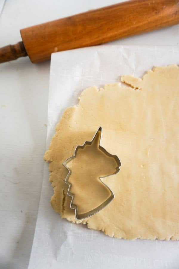cutting unicorn out of sugar cookie dough
