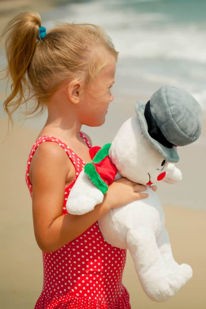 young girl holding a stuffed snowman standing on the beach