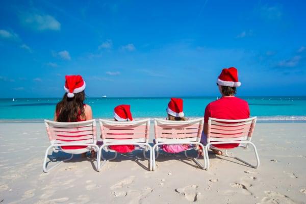 family sitting in beach chairs facing ocean wearing Santa hats