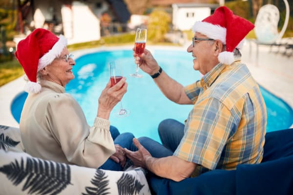 Happy mature couple in Santa hats by the pool
