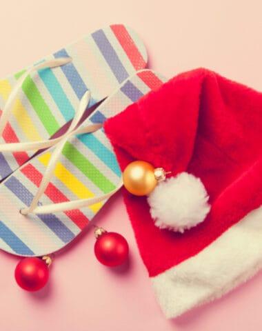 Santas hat and flip flops on pink background