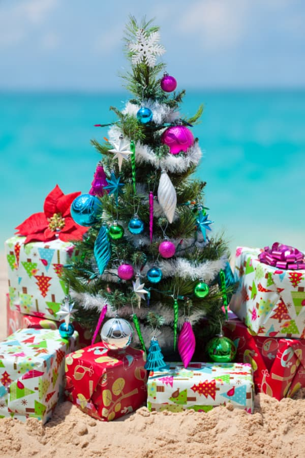 Small decorated Christmas tree on the beach with gifts underneath it