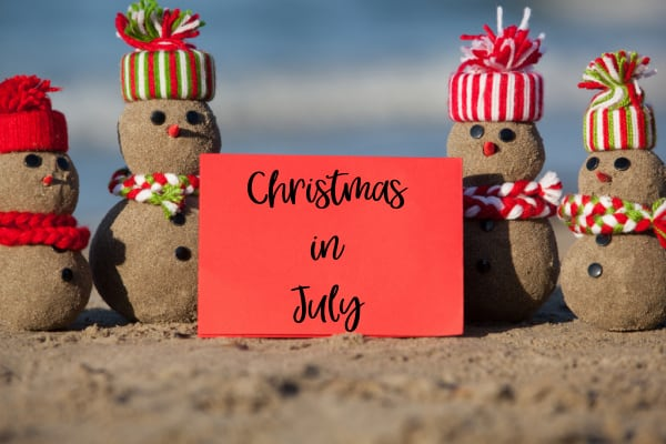small snowman family on beach with a sign that says Christmas in July