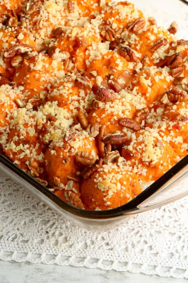 twice baked sweet potato casserole with bacon in baking dish on a white doily