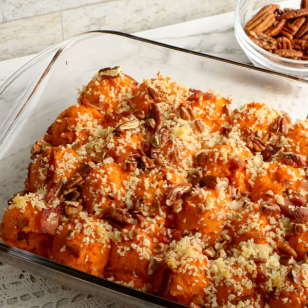 twice baked sweet potato casserole with bacon in baking dish next to a bowl of pecan halves